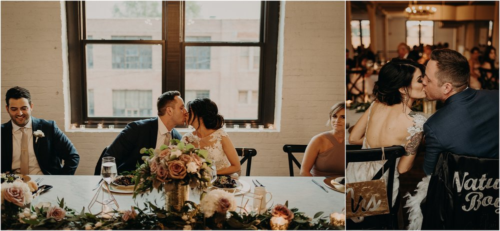 The happy couple kisses as they sit down for dinner in their bride and groom hot seats