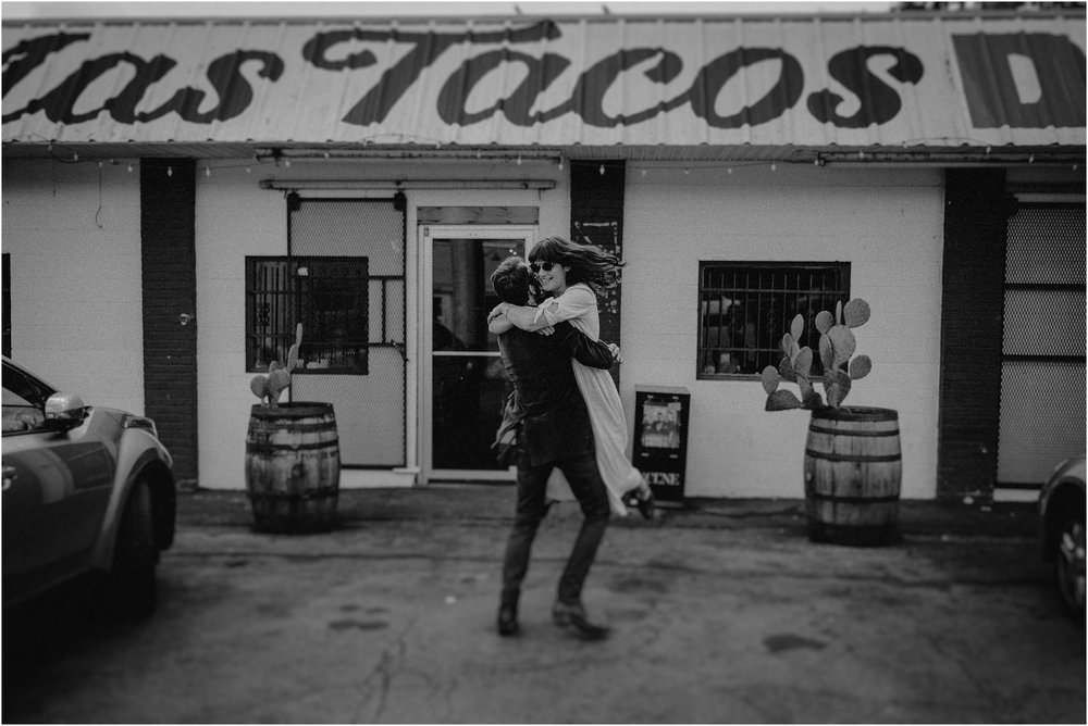 The groom spins his bride outside of Mas Tacos