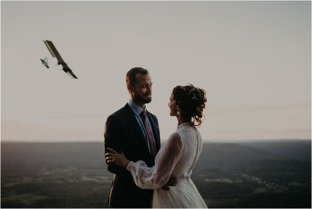Couple stand on the edge of a mountain as a plane flies by in the background