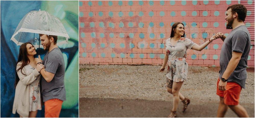 Happy couple dances in the rain in front of urban murals