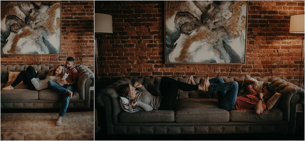 Couple plays footsie on the couch of their home during an engagement session