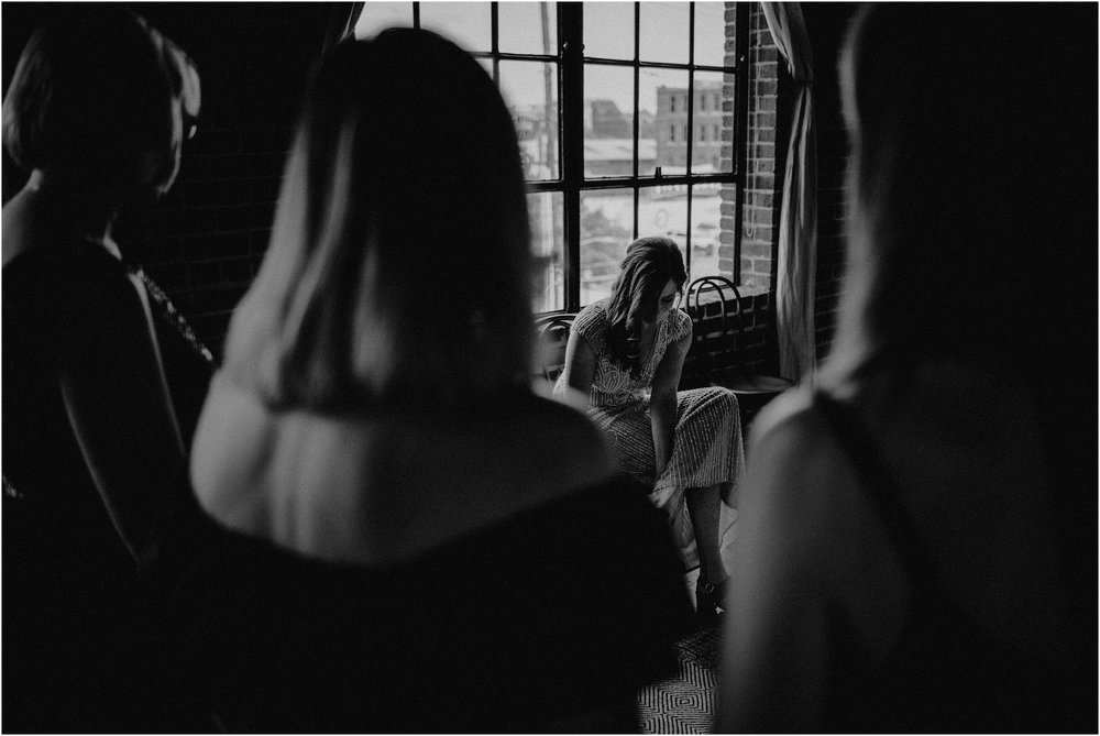The bridesmaids and mother of the bride look on as the bride fastens her shoes