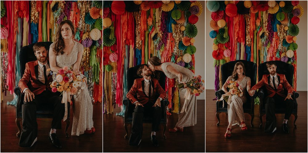 The bride and groom pose in a vintage velvet chair in front of their festive vibrant background ceremony arch designed by Southerly Flower Farms