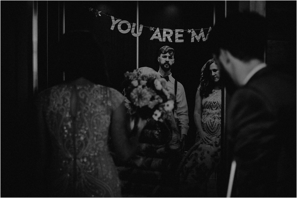 The bride and groom enter the elevator where a life-size cardboard cut-out of the couple awaits their guests