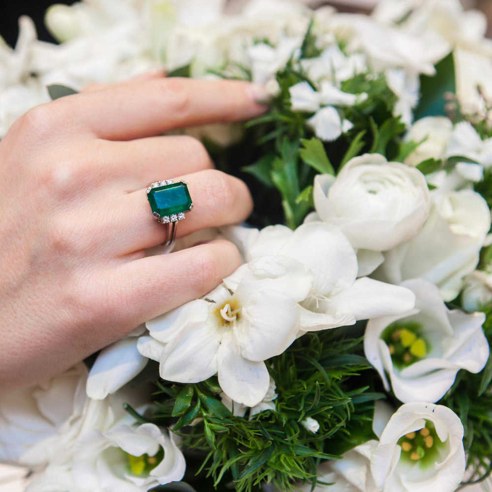 An emerald and diamond ring.The cut-cornered rectangular emerald, weighing approximately 2.55 carats, to tapered baguette-cut diamond two stone shoulders.