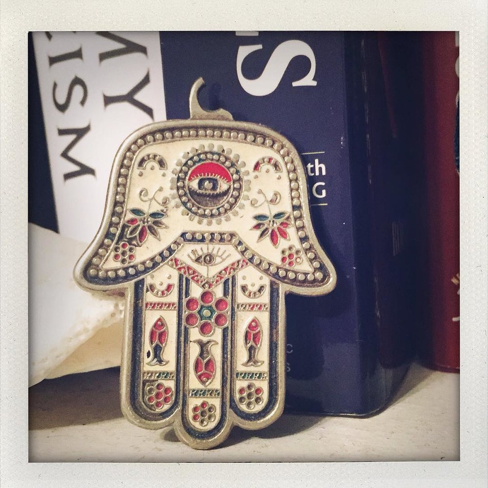 Late Night Hamsa. La Main de Fatima. Cleaning and clearing my space and found this part of a key chain I bought when my dad lived in Tunis. I've always been a mystic darling before I even knew it. I love symbols and I've been surrounding myself with all kinds of symbols. The history of the symbol goes as far back as Mesopotamia and connects to Mary, Judiasm, Islam, Buddha, Isis, Osiris & Horus. It reminds me we are more interconnected then we believe. I love the three fishes in mine. #hamsa #protection #divine #thirdeye #amulet (at New York, New York)