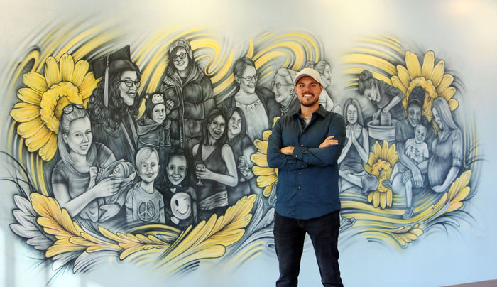 Lindsey Bauman/The Hutchinson News Artist and designer Brady Scott stands with his completed mural inside Hutchinson Clinic Women's Care on Monday. A dedication is scheduled for today from 6 to 7:30 p.m.