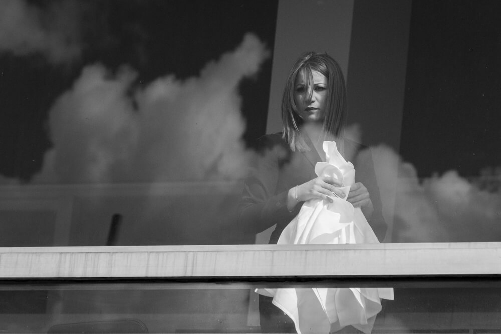 A candid photograph of a young lady with the reflections of the clouds, taken at South Bank in London