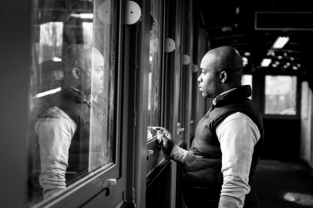 A photograph of man and his reflection in the windows, taken at the Gravesend railway station