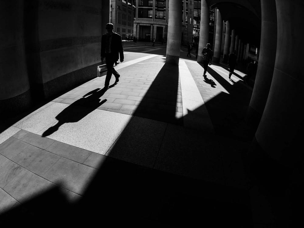 A high contrast photograph with shadows of people taken near London Stock Exchange using a Fisheye lens