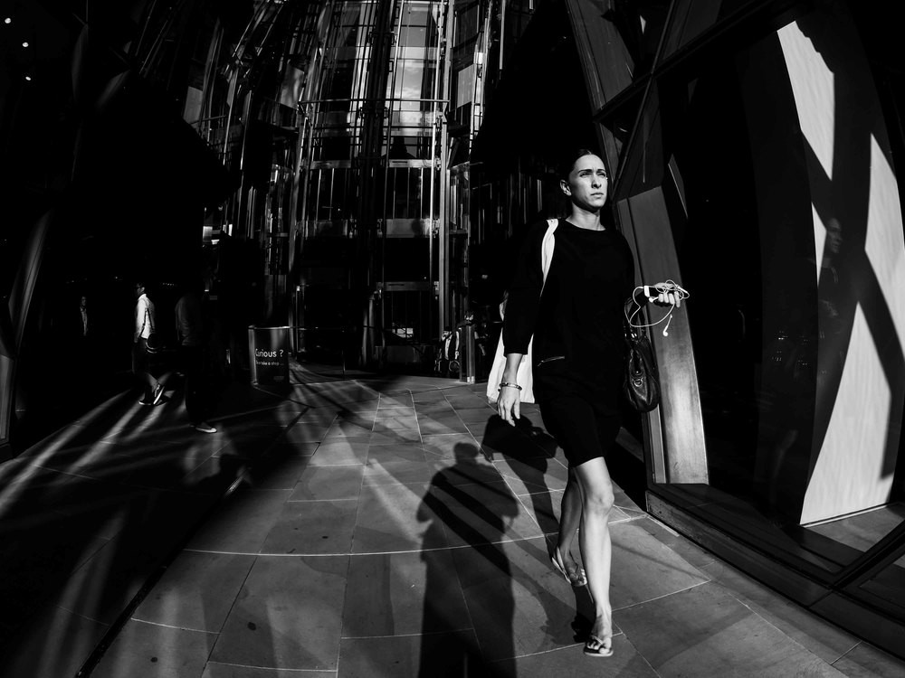 A photograph of a young lady walking out the One New Change shopping mall opposite St. Pauls in London, captured using a Fisheye lens.