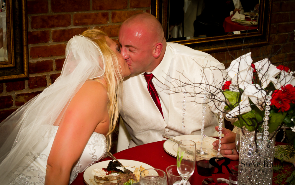 Bride and Groom enjoying a kiss at the table