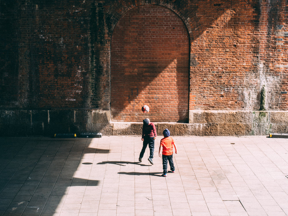 london-kids-playing-football-brick-wall