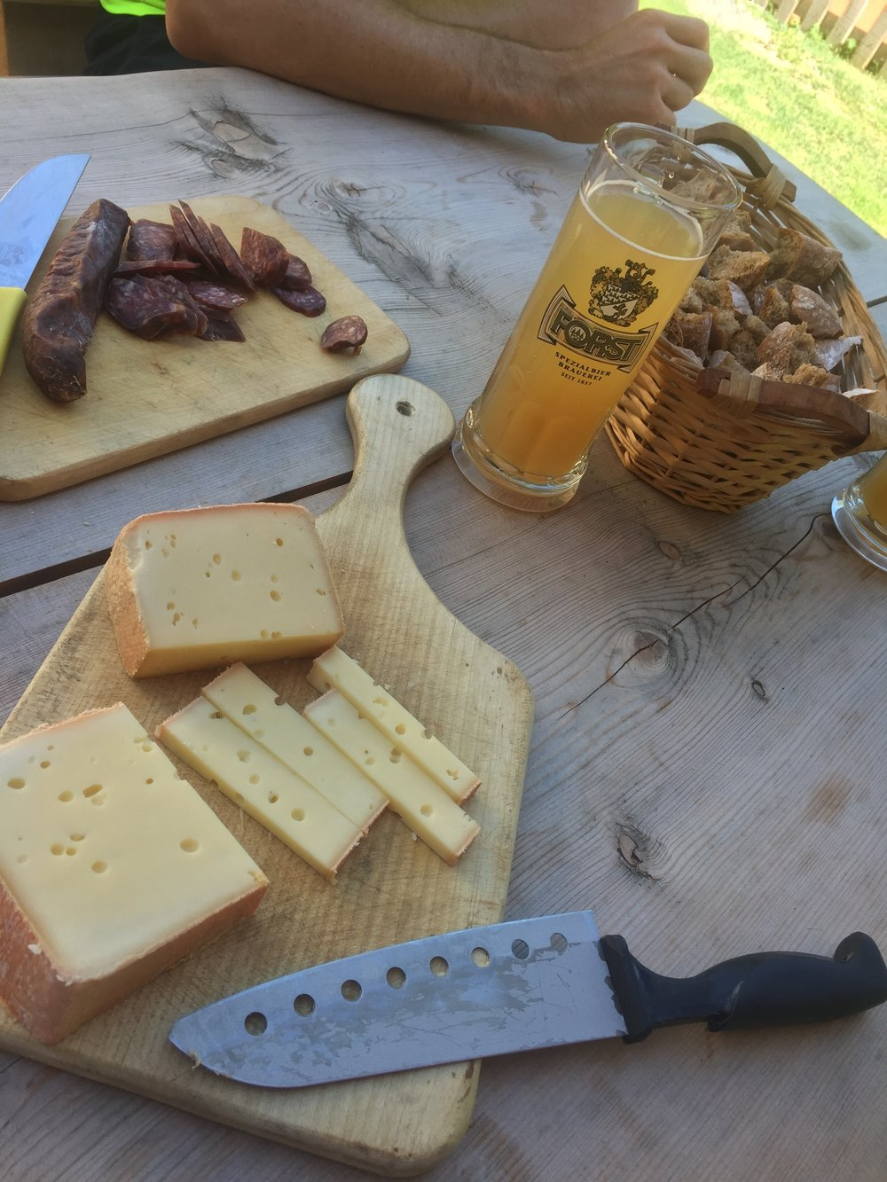 Homemade cheese, sausages, apple juice and bread