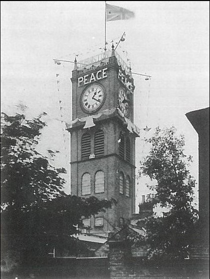"Gillett & Johnston was a clockmaker and bell foundry based in Croydon, England from 1844 One of the four sample clockfaces was restored by Gillett & Johnston 2002 and used in Gudrun´s installation ""Time"" 2002, image: The Gillett & Johnston former clocktower in Union Road decorated for peace celebrations in 1919 at the end of the First World War."