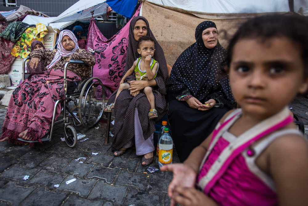 A family is seen in the improvised camp in the Al-Shifa Hospital, where families have sought refuge of the Israeli attacks. Gaza. 2014.