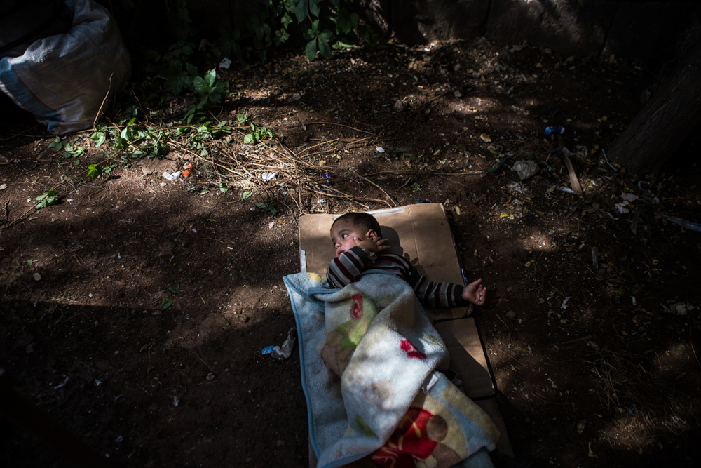 A Syrian Kurd refugee baby, fleeing the ISIS offensive against Kobane (Ayn al-Arab) in Syria, lies on the ground in the cultural center of Suruç, Turkey. 2014.