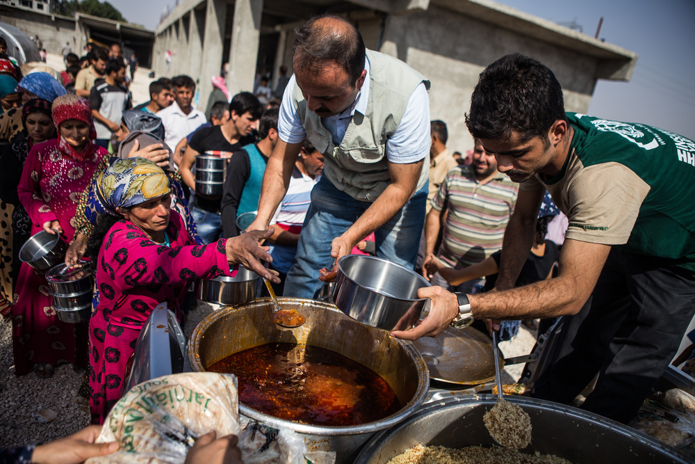 Syrian Kurds refugees, fleeing the ISIS offensive against Kobane (Ayn al-Arab) in Syria, wait in line to receive food in a temporary refugee camp in Suruç, Turkey. 2014.