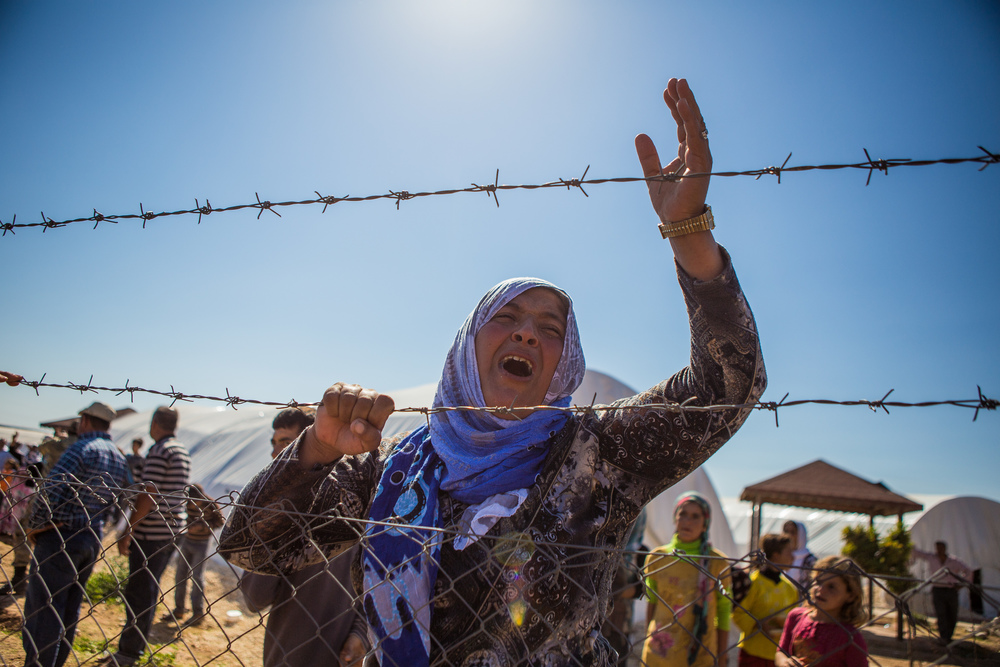 A woman in a refugee camp in the Turkish/Syrian border in Mursitpinar, gestures as shelling takes place in Kobane (Ayn al-Arab). Turkey. 2014.