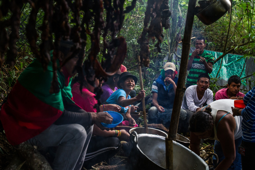 Some members of the Nasa community, sit together in the camps they have built in the land taken, many camps for staying and cooking are spread around the land they have taken. Colombia. 2015.