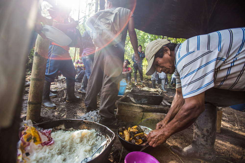 Some members of the Nasa community , prepare food in the camps they have built in the land taken, many camps for staying and cooking are spread around the land they have taken. Colombia. 2015.