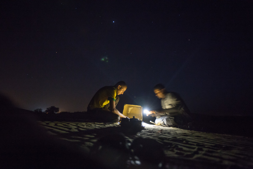 Tuareg men prepare a fire in the Sahara dessert near Ghat.