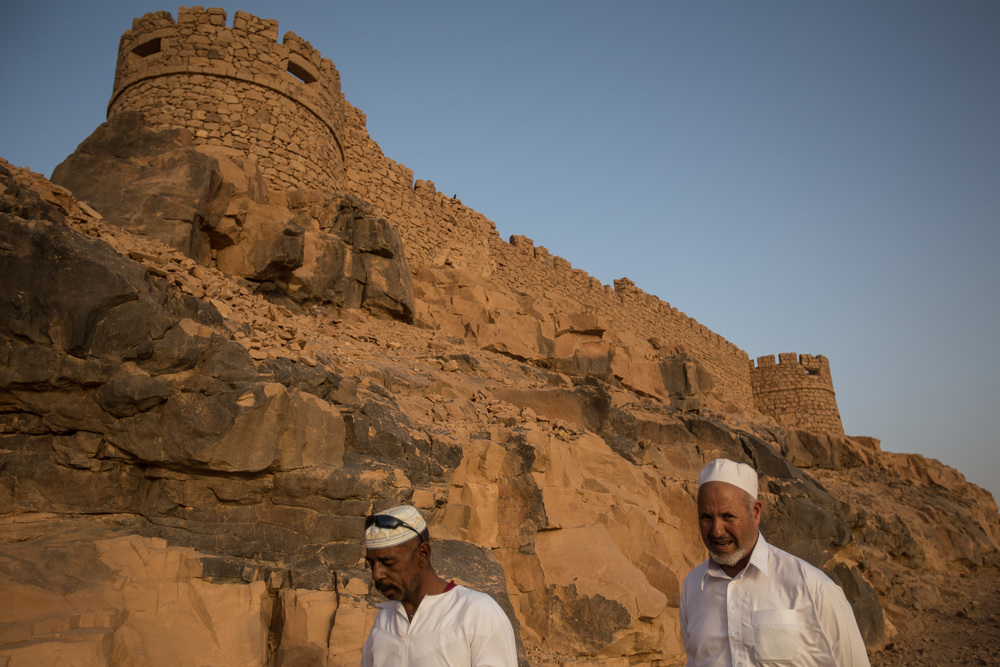 Men walk through the ancient medina of Ghat once a tourist attraction lays unprotected and has been used occasionally for shelter for migrants and refugees from Ubari, bearing the risk of damage to the ancient site.