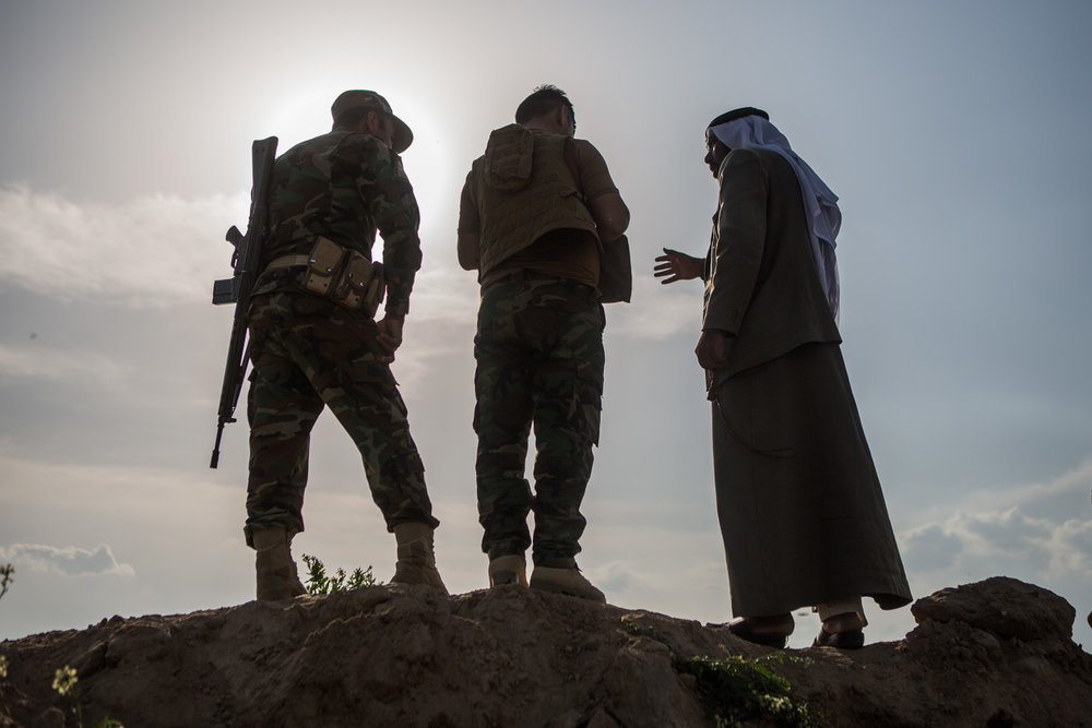 Peshmerga soldiers and a local tribe leader look ahead in the frontline of Makhmour.