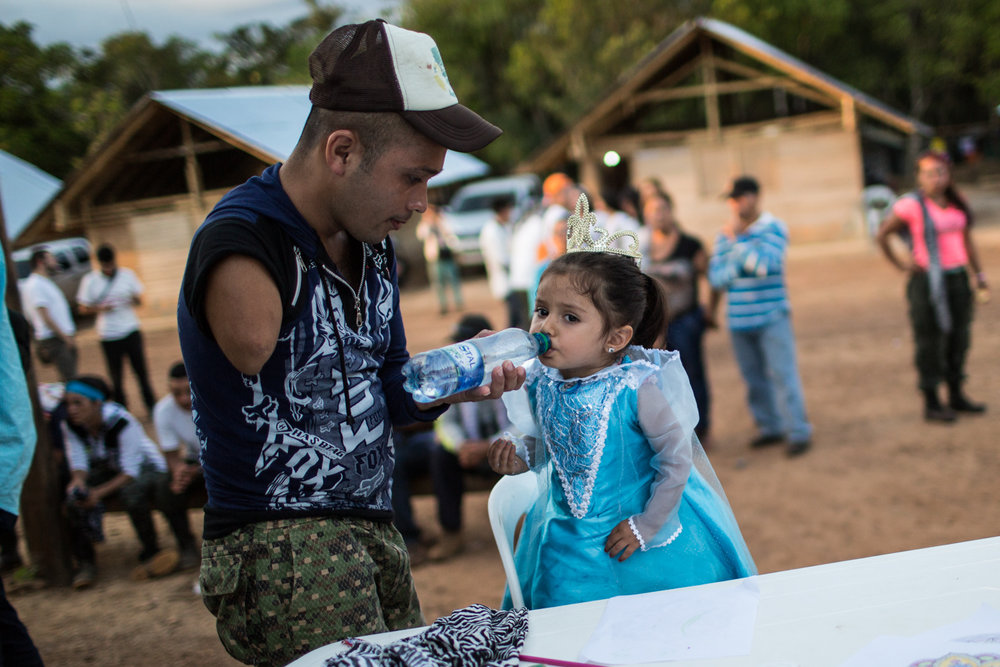 A member of the FARC with an amputee arm interacts with a girl who attended the vigil with her family.