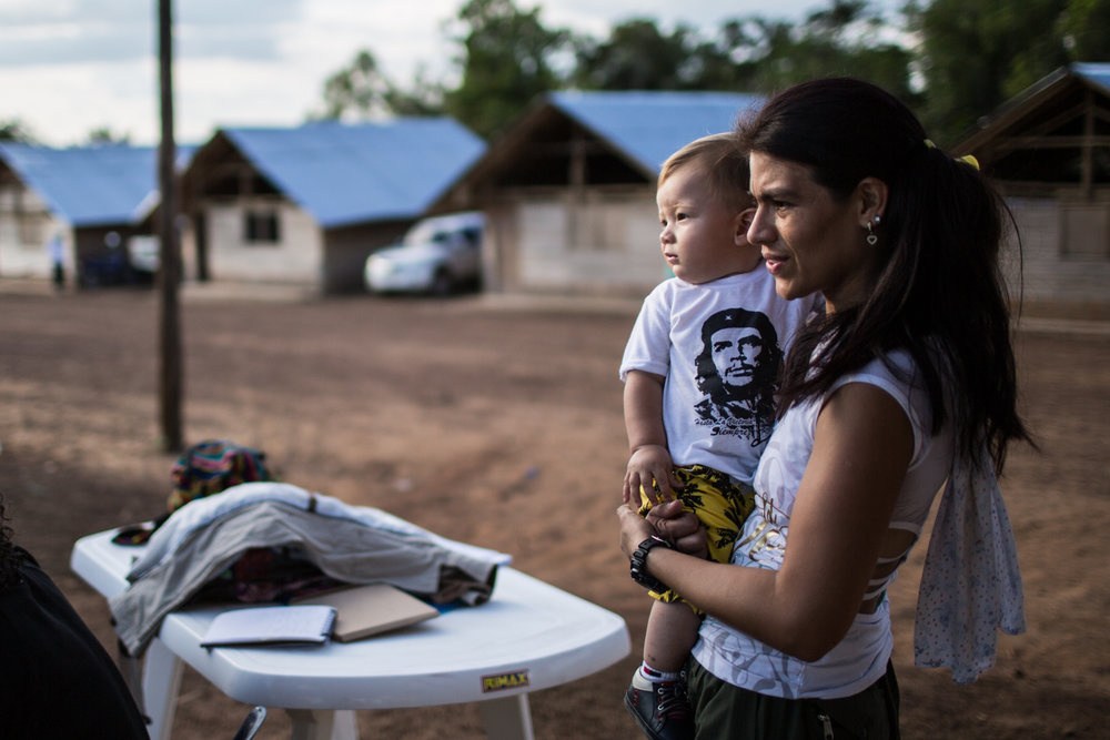 A FARC woman stands during the vigil with her 1 year old son, some women fighters are beginning to think of motherhood, having babies used to be banned by the FARC regulations.