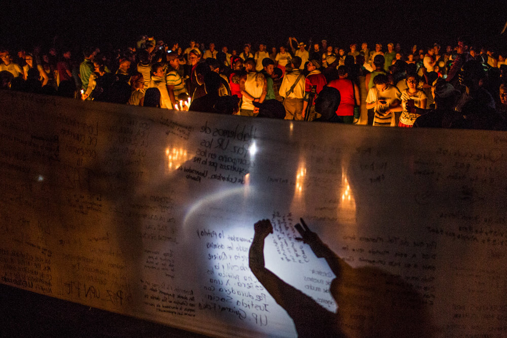 The attendees write messages in support of the peace process while chanting and doing a small walk in the vigil for peace that was summoned nationally and replicated in camps across Colombia.