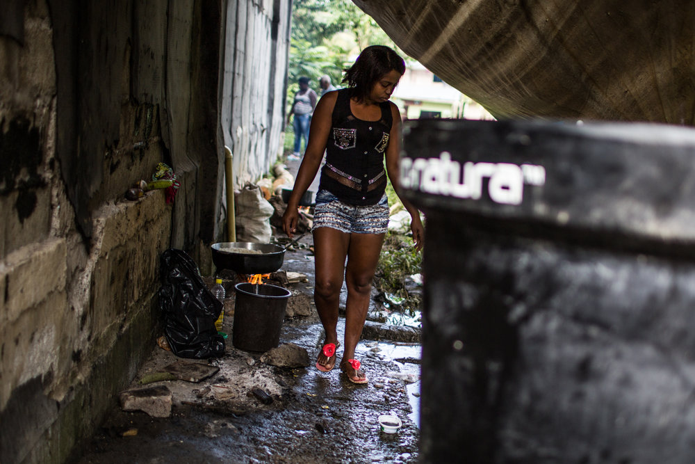 A woman walks near an improvised water tank and kitchen in a camp near the shelter.