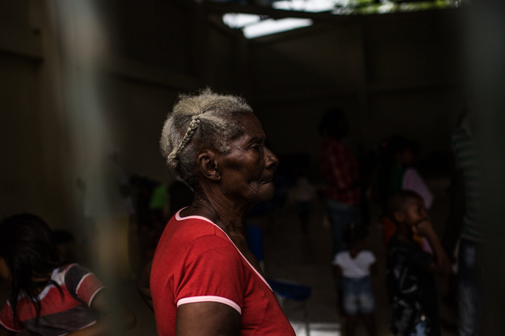 A displaced elder waits inside the shelter, she has been displaced over 4 times in the last 2 decades.