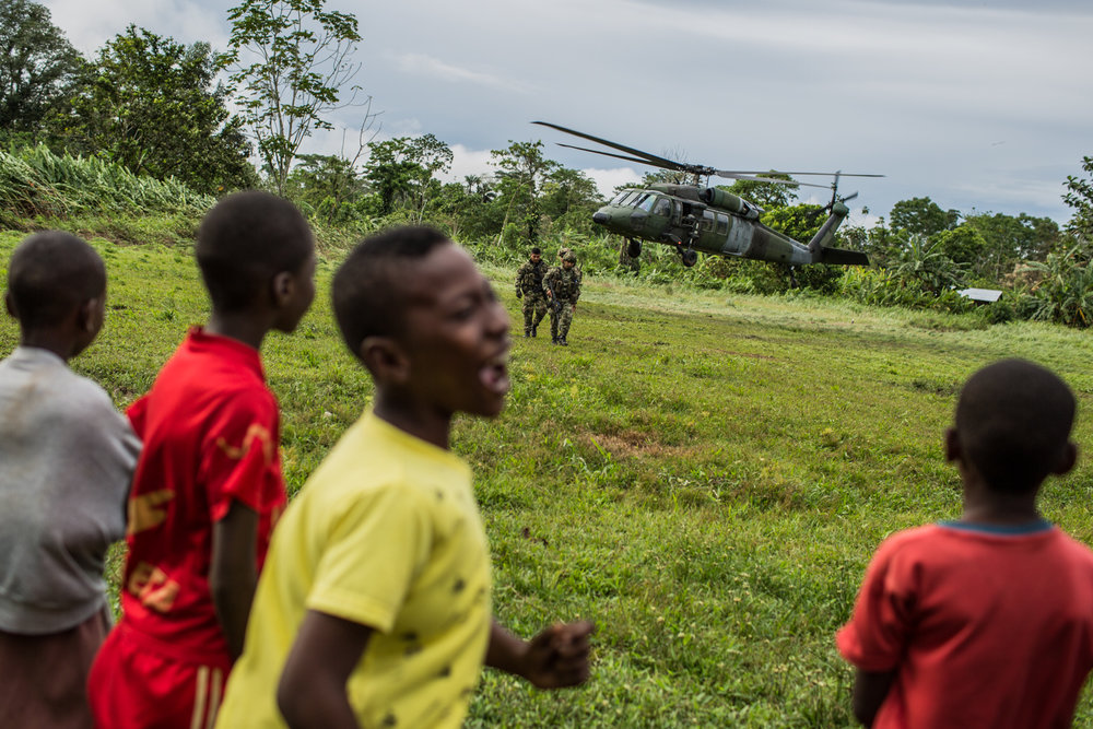 Kids wait for the arrival of a Colombian army helicopter that is transporting 2 Generals that are going to talk to the community and leave troops to the area.