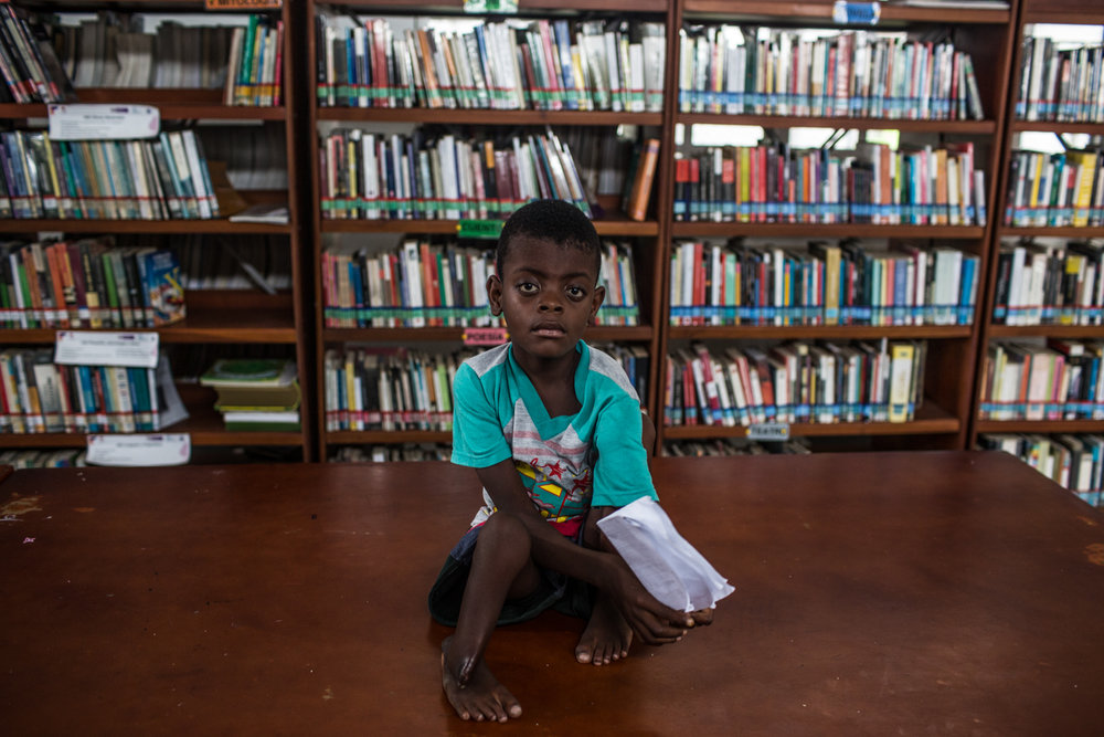 A displaced child waits in the local library of Pie de Pato that serves as a medical facility to attend the displaced person that arrived.