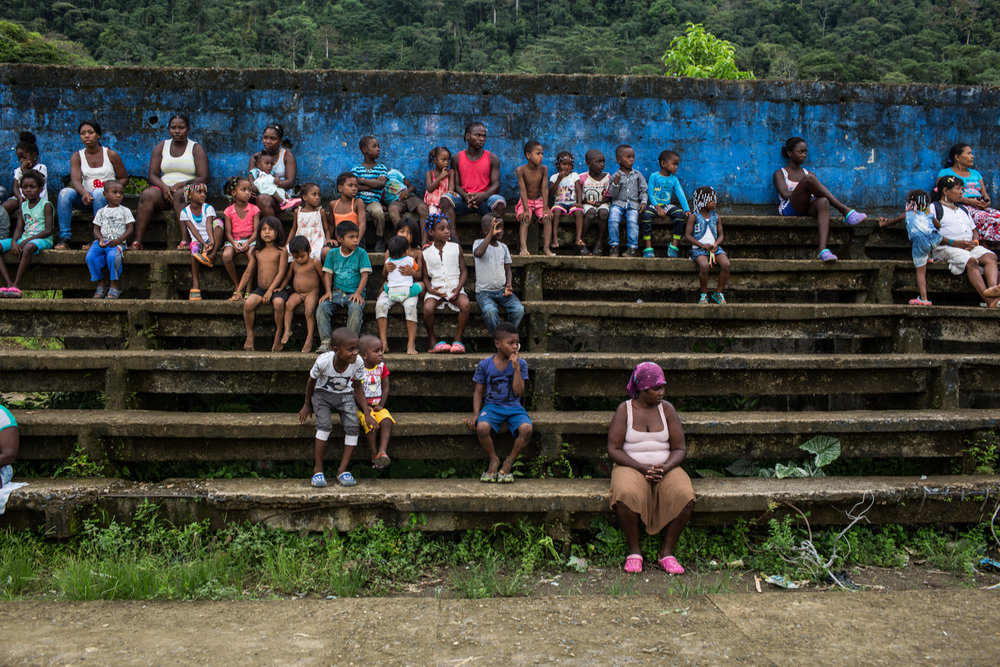 A group of displaced people wait in the park of the Pie de Pato.