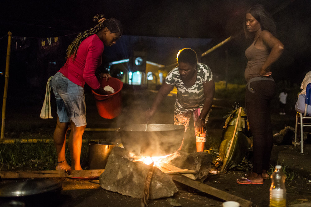Displaced women prepare dinner in an improvised kitchen.