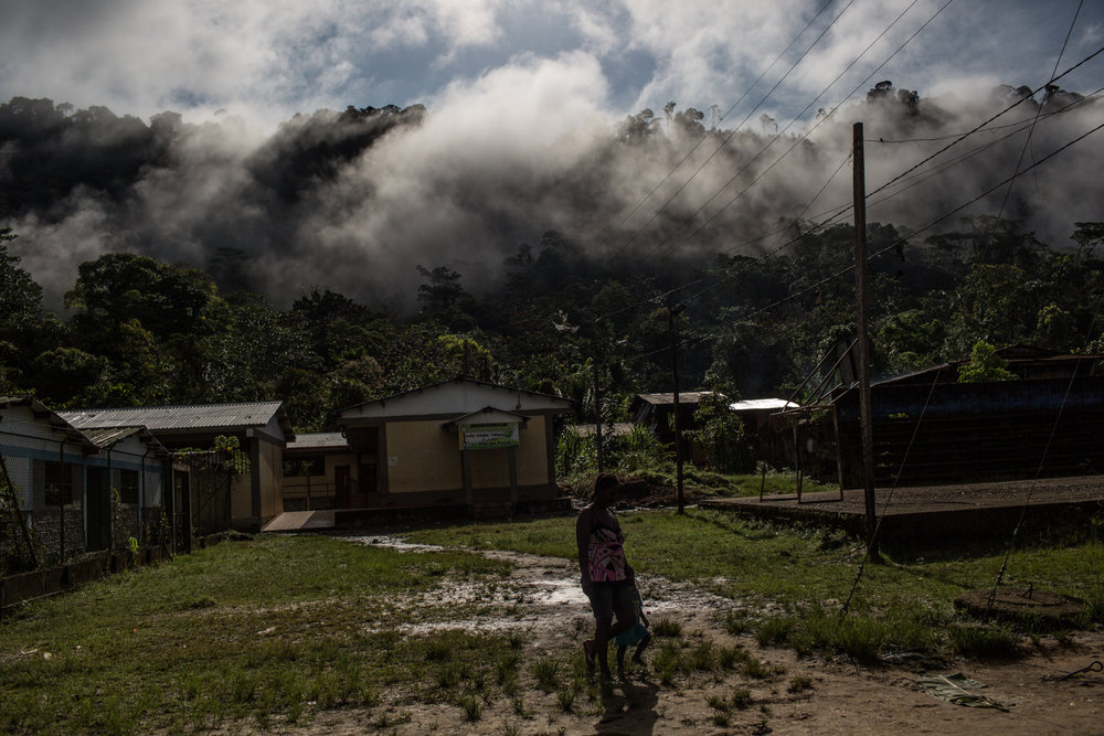A mother and her children walk near the temporary shelter of Pie de Pato.