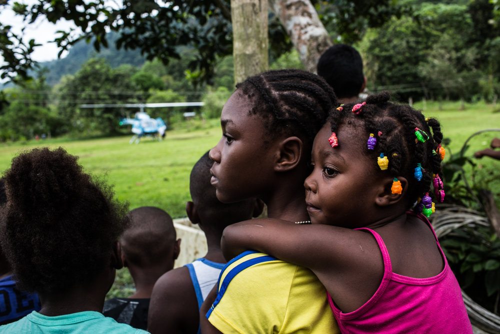 Displaced children wait near a helicopter that landed near the shelter.