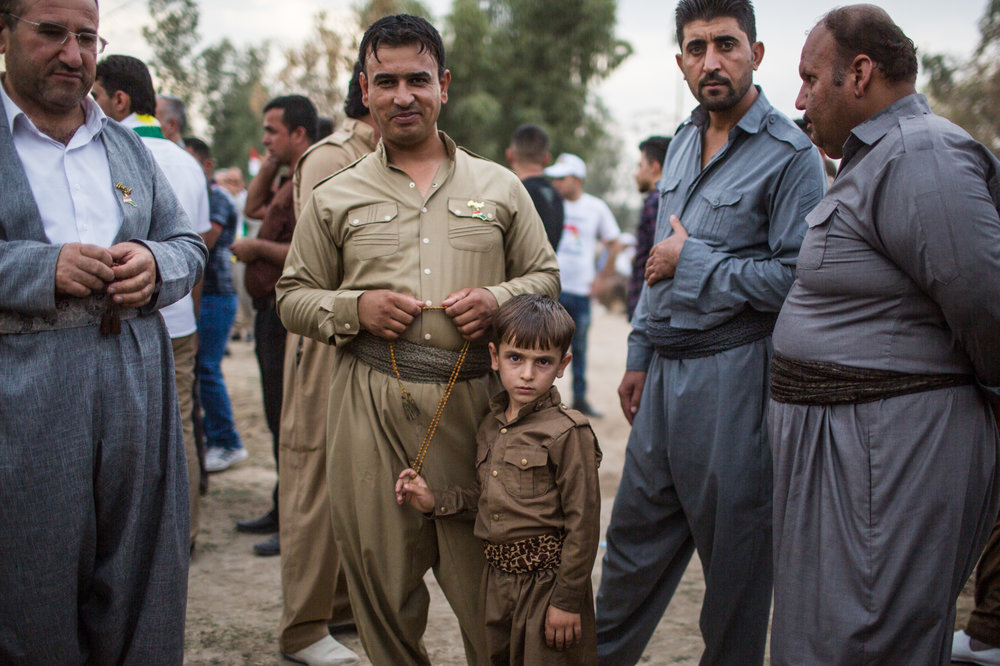 Kurdish father and son attend a rally in the heavily contested city of Tuz Khormato. south of Kirkuk.