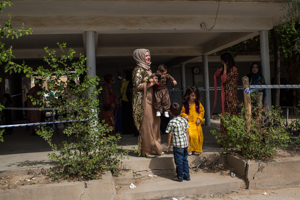 A woman and his kids arrive at a voting station prepared in a school in Kirkuk city.