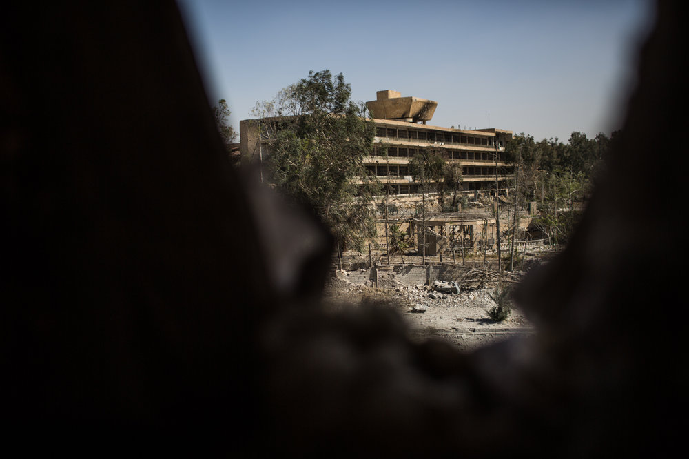 The national hospital where there is a large number of civilians is seen through a hole in a SDF forward position in the west frontline of Raqqa at about 600 meters.