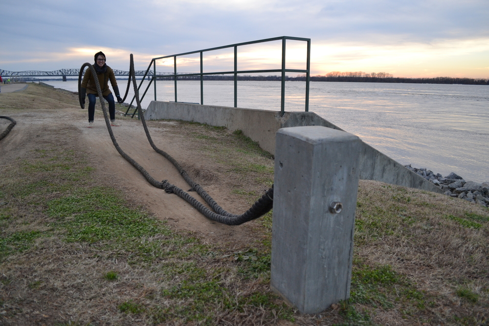 Mel pretends her little baby arms can lift the exercise ropes on the riverfront in Memphis, TN.