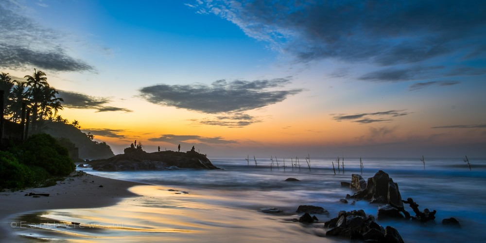 A wide angle view across the beach of Weligama, Sri Lanka during morning twilight.