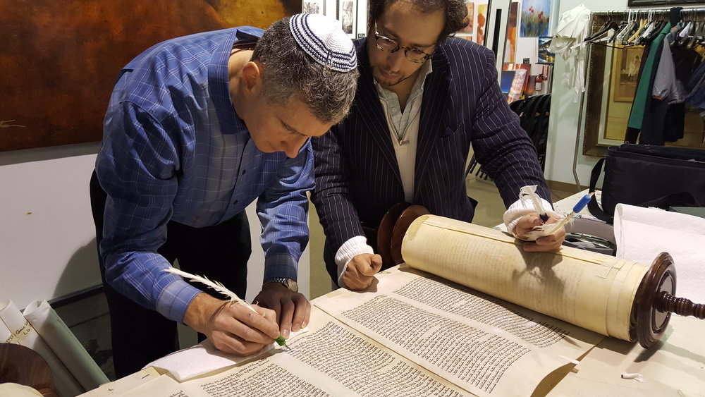 Cantor Abramowitz completes a letter in the Torah
