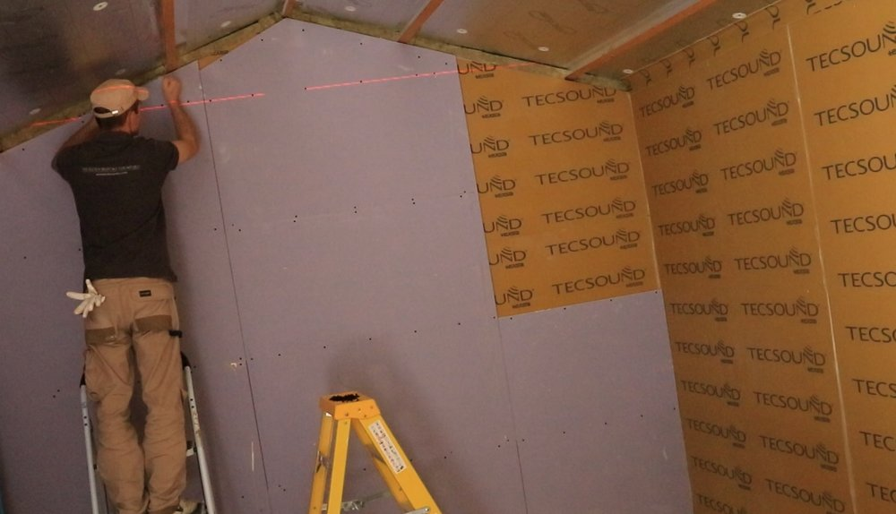 The first layer of plasterboard installed with TECSOUND covered. Builders installing the second layer of plasterboard on top of TECSOUND