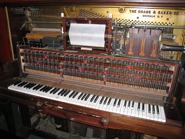 ... and a vintage mechanical player piano showing the roll-reading mechanism.