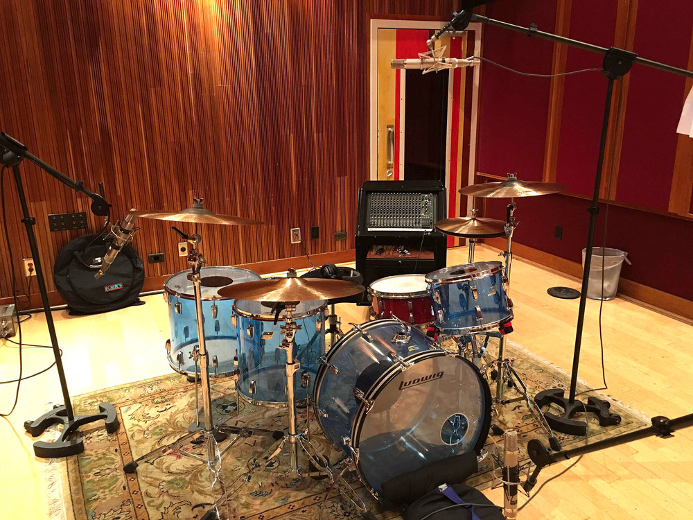 The three close mics were placed in front of the kick drum, overhead, and to the right of the low tom looking toward the snare and rack tom. The three mics were panned center in the mix.