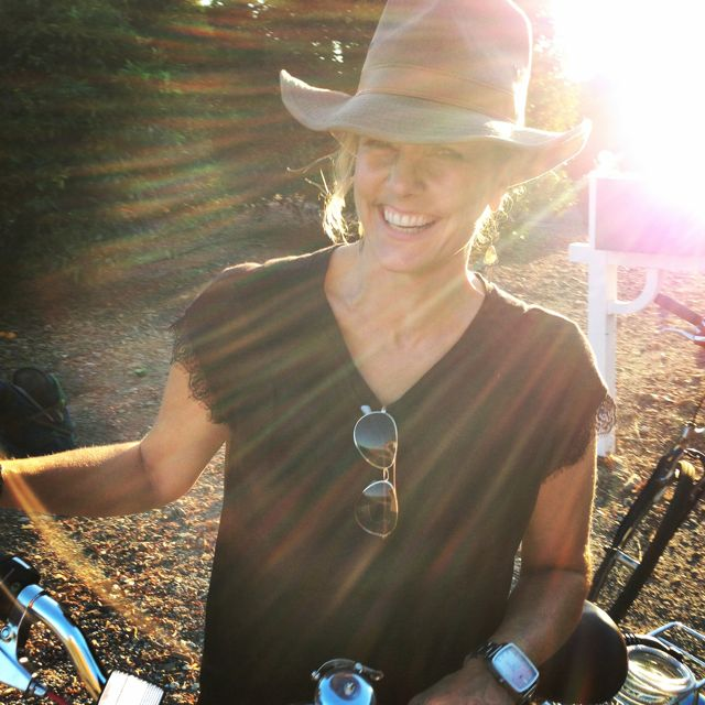 Founder, Michele Melonas, riding her bike through orange groves in Ojai.