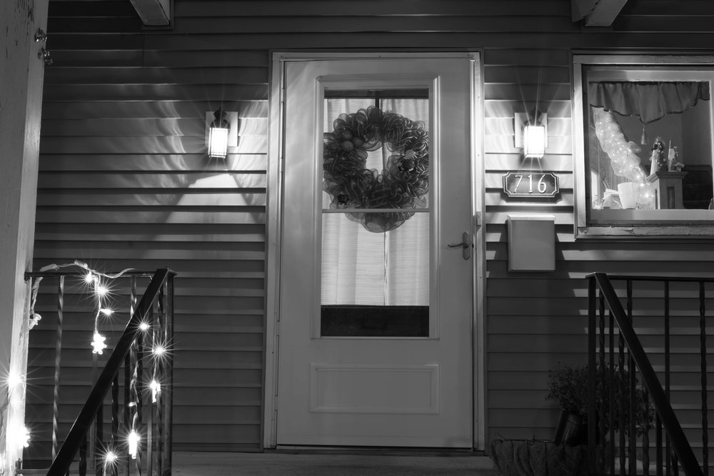 My parent's front door. Taken early in the week, before decorations were taken down. My mom and I made matching wreaths together this year. I like the little things about this picture. The plant overtaken by frost in the bottom corner, the lopsided Christmas lights I put up, and most importantly the little cone Santas, snowman, and tree sitting at the bottom of the banister, where they are almost always displayed at Christmas. Crafts my brother and I made in art class during elementary school.This is my view each time I come home, and the added Christmas things make it feel especially warm and inviting.